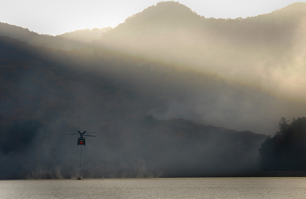 A South Carolina Army National Guard CH-47 Chinook helicopter supports the South Carolina Forestry Commission to contain a fire near Table Rock, S.C. Droughts — exacerbated by climate change — cause fire dangers throughout much of the United States. © Army Staff Sgt. Roberto Di Giovine